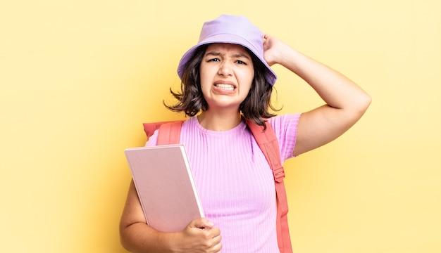 젊은 히스패닉 여성은 머리에 손을 얹고 스트레스를 받거나 불안해하거나 무서워합니다. 학교 개념으로 돌아가기