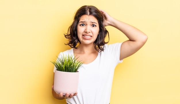 若いヒスパニック系の女性は、頭に手を置いて、ストレス、不安、または恐怖を感じています。成長の概念