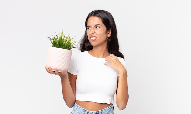스트레스, 불안, 피곤, 좌절감을 느끼고 장식용 식물을 들고 있는 젊은 히스패닉 여성