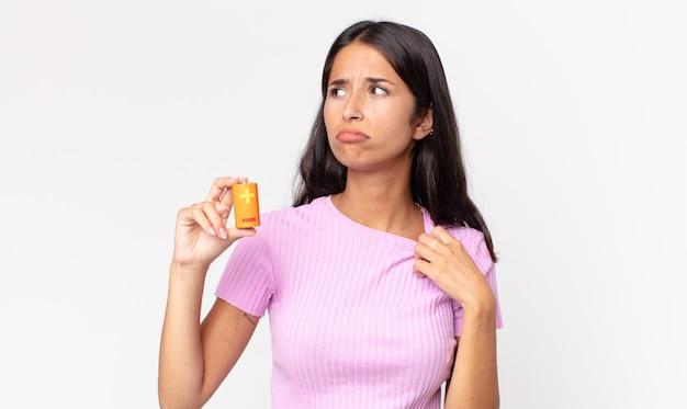 Молодая латиноамериканская женщина чувствует стресс, тревогу, усталость и разочарование и держит батарейки