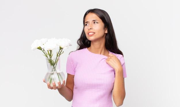 若いヒスパニック系の女性は、装飾的な花を持ってストレス、不安、疲れ、欲求不満を感じています