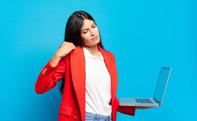 Молодая латиноамериканка чувствует стресс, тревогу, усталость и разочарование, тянет рубашку за шею и выглядит разочарованной из-за проблемы. концепция ноутбука