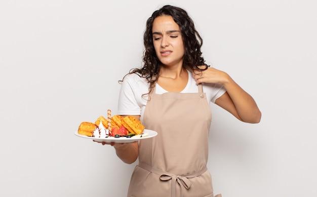 Молодая латиноамериканка чувствует стресс, тревогу, усталость и разочарование, тянет рубашку за шею, выглядит расстроенной проблемой