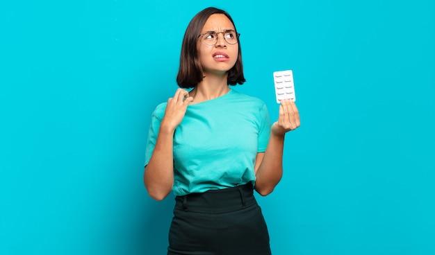 ストレス、不安、疲れ、欲求不満を感じ、シャツの首を引っ張って、問題に不満を感じている若いヒスパニック系女性