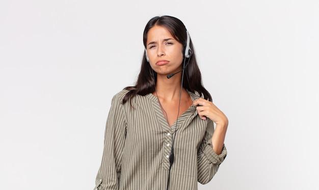 Молодая латиноамериканская женщина чувствует стресс, тревогу, усталость и разочарование с помощью гарнитуры. концепция телемаркетинга