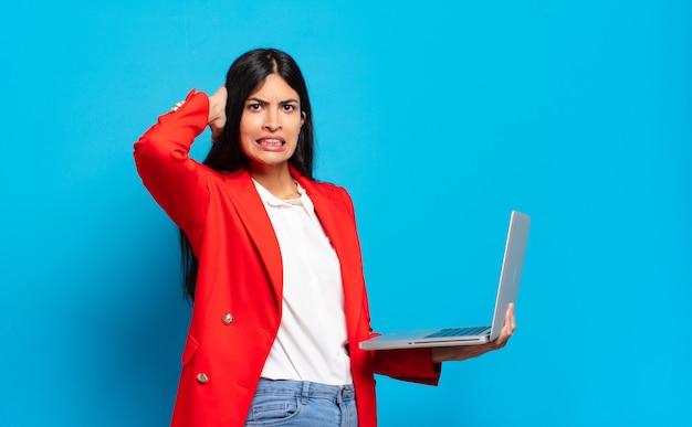 젊은 히스패닉계 여성은 머리에 손을 얹고 실수로 당황하고, 스트레스를 받고, 걱정하고, 불안하거나 무서워합니다. 노트북 개념