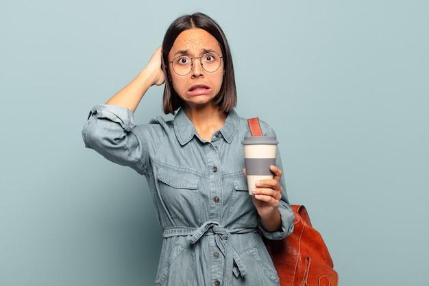 ストレス、心配、不安、または恐怖を感じ、頭に手を置いて、誤ってパニックに陥っている若いヒスパニック系女性