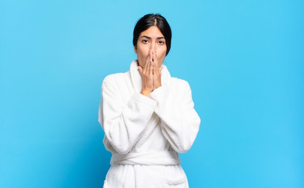 Young hispanic woman feeling worried, upset and scared, covering mouth with hands, looking anxious and having messed up. bathrobe concept
