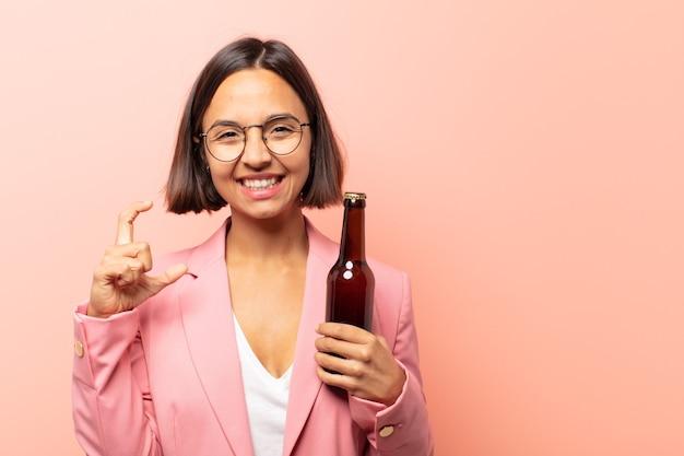 Молодая латиноамериканская женщина, обрамляющая или очерчивающая собственную улыбку обеими руками, выглядящая позитивно и счастливой, концепция здоровья