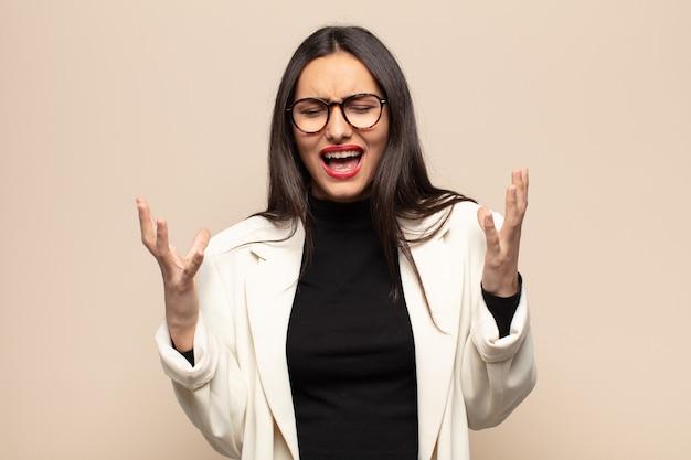 Молодая латиноамериканка яростно кричит, чувствуя стресс и раздражение, подняв руки вверх, говоря, почему я