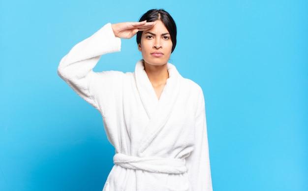 존경을 표시하는 명예와 애국의 행위에서 군사 경례와 함께 카메라를 인사하는 젊은 히스패닉 여성