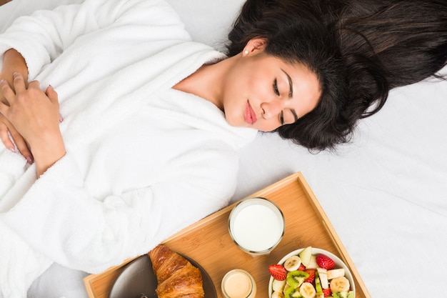 Young hispanic woman having breakfast on the bed