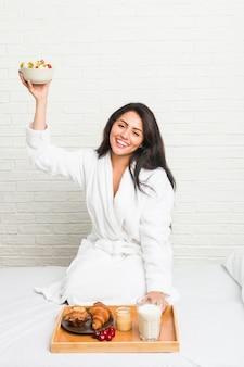 Молодая испанская женщина завтракает на кровати