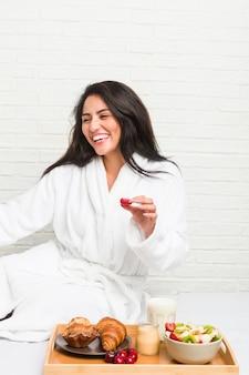 ベッドで朝食をとっている若いヒスパニック系女性