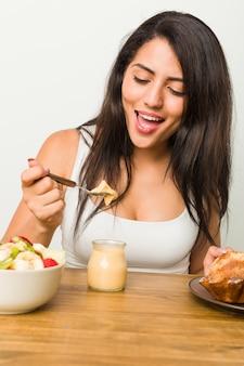 테이블에 아침을 먹고 젊은 히스패닉 여자
