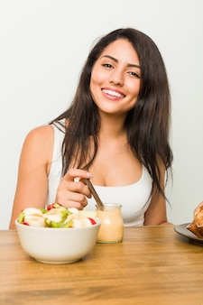 Young hispanic woman having breakfast on the table