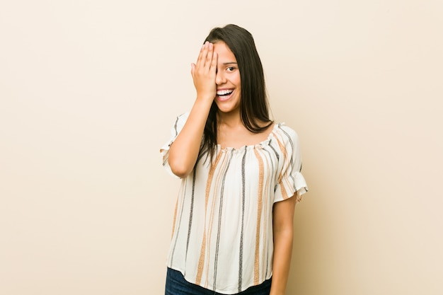 Young hispanic woman having fun covering half of face with palm.