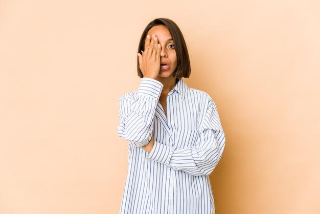 手のひらで顔の半分を覆うことを楽しんでいる若いヒスパニック系女性。 Premium写真