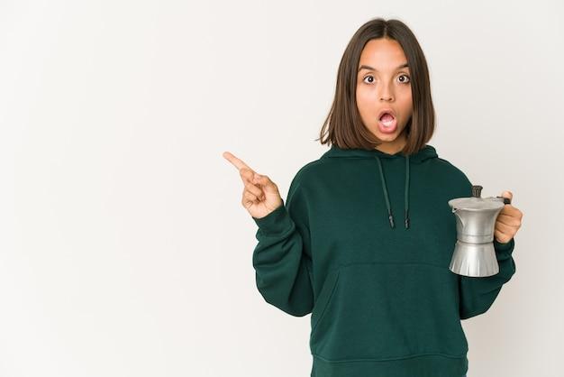 横を指しているコーヒーメーカーを保持している若いヒスパニック系女性