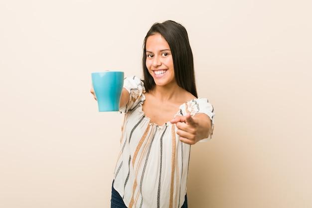 Молодая испанская женщина, держа чашку веселые улыбки, указывая на фронт.