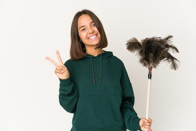 指で平和のシンボルを示す、楽しくてのんきなダスターを持っている若いヒスパニック系の女性。