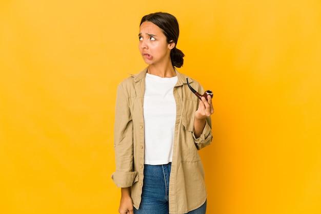 담배 파이프를 들고 젊은 히스패닉 여성이 혼란스러워하고 의심스럽고 확신이 없습니다.
