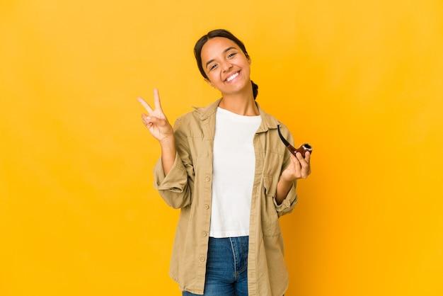Молодая латиноамериканская женщина, держащая курительную трубку, радостная и беззаботная, показывая пальцами символ мира.
