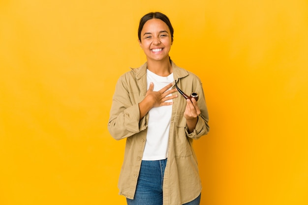Молодая латиноамериканская женщина, держащая курительную трубку, громко смеется, держа руку на груди.