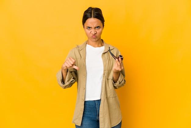 Молодая латиноамериканская женщина, держащая курительную трубку, показывает жест неприязни, палец вниз. концепция несогласия.