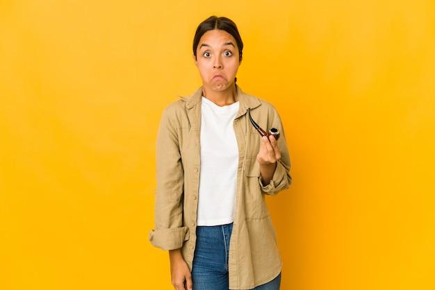 喫煙パイプを持っている若いヒスパニック系女性は肩をすくめると混乱した目を開いています