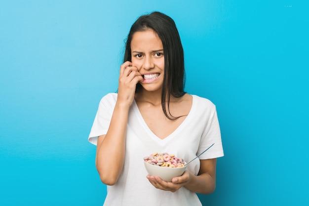 Молодая латиноамериканская женщина, держащая сахарную кашу, кусающую ногти, нервная и очень взволнованная.