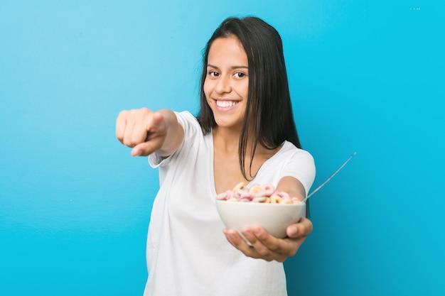 Молодая испанская женщина держа шар хлопьев сахара жизнерадостные улыбки указывая к фронту.