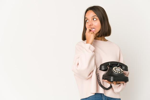빈티지 전화를 들고 젊은 히스패닉 여자 복사본 공간을보고 뭔가 대 한 편안한 생각을 격리합니다.