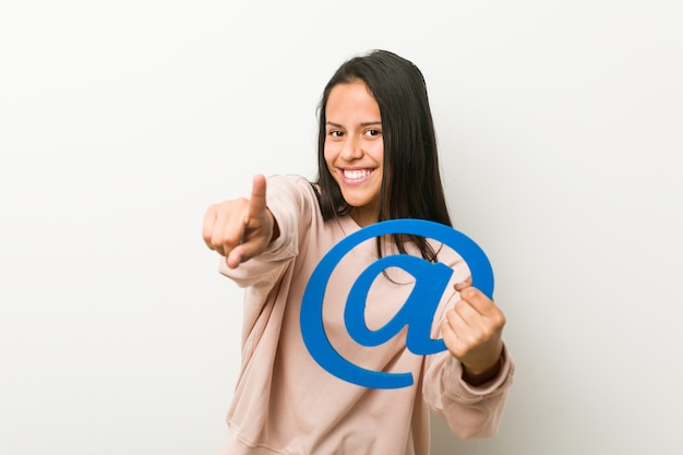 Молодая испанская женщина, держащая на значок веселые улыбки, указывая на фронт.