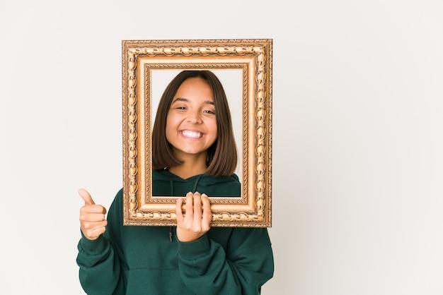 笑顔と親指を上げて古いフレームを保持している若いヒスパニック系女性