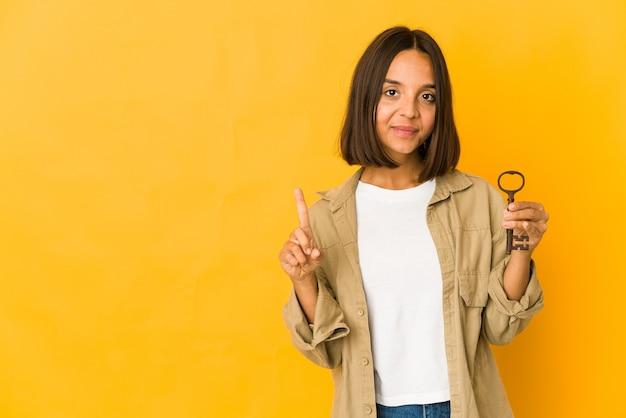 指でナンバーワンを示す古いキーを保持している若いヒスパニック系女性。