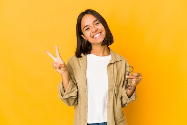 指で2番目を示す古いキーを保持している若いヒスパニック系の女性。