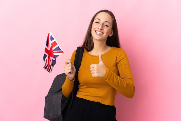 Молодая латиноамериканская женщина, держащая флаг соединенного королевства, жестом показывает палец вверх