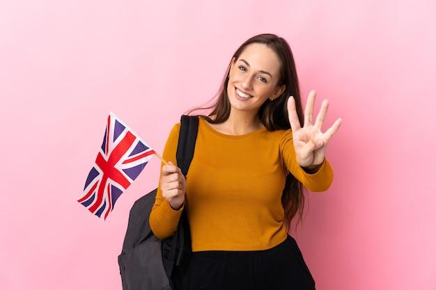 Молодая латиноамериканская женщина, держащая флаг соединенного королевства счастлива и считая четыре пальцами