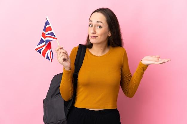손을 올리는 동안 의심을 갖는 영국 국기를 들고 젊은 히스패닉 여자