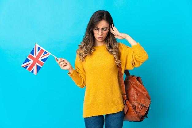 Молодая латиноамериканская женщина, держащая флаг соединенного королевства изолирована на синем пространстве, разочарована и закрывает уши