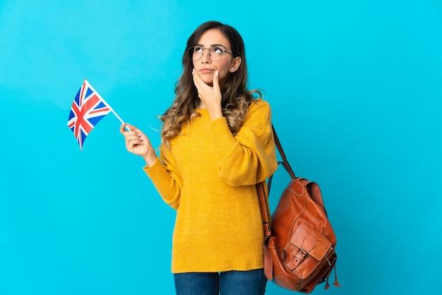Молодая латиноамериканская женщина, держащая флаг соединенного королевства, изолированная на синей стене с сомнениями