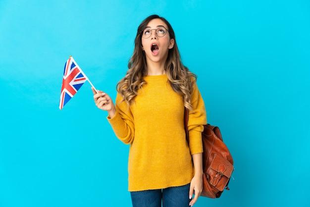 Молодая латиноамериканская женщина, держащая флаг соединенного королевства, изолированная на синей стене, смотрит вверх и с удивленным выражением лица