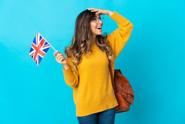 Молодая латиноамериканская женщина, держащая флаг соединенного королевства, изолированная на синей стене, много улыбаясь