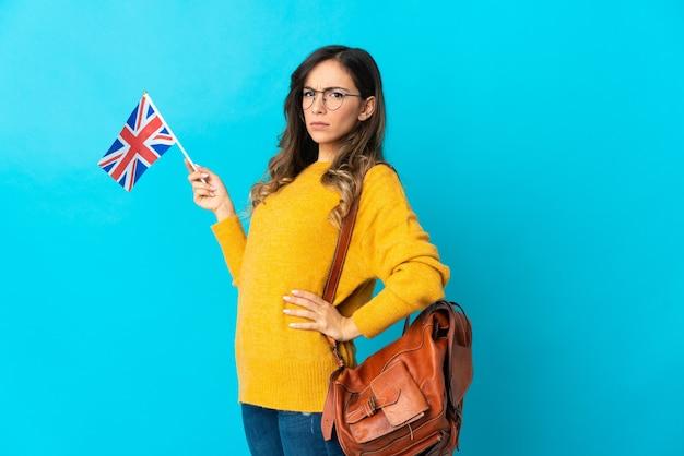Молодая латиноамериканская женщина, держащая флаг соединенного королевства, изолированная на синей стене, страдает от боли в спине из-за того, что приложила усилие