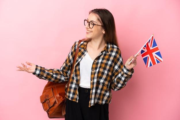 側面を見ながら驚きの表情でピンクの背景に分離されたイギリスの旗を保持している若いヒスパニック系女性