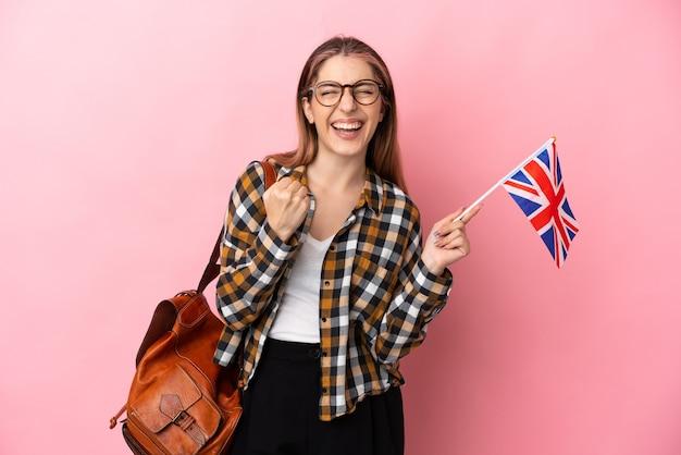 勝者の位置での勝利を祝うピンクで隔離のイギリスの旗を保持している若いヒスパニック系女性