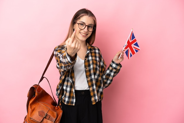 来るジェスチャーをしているピンクで隔離のイギリスの旗を保持している若いヒスパニック系女性