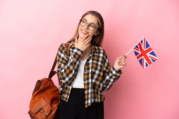 笑顔で見上げるピンクで隔離のイギリス国旗を保持している若いヒスパニック系女性