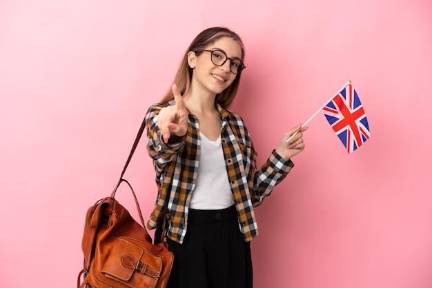 ピンクの表示と指を持ち上げて分離されたイギリスの旗を保持している若いヒスパニック系女性